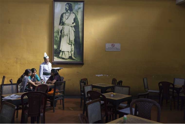 The Palaces of Memory ©Stuart Freedman, A waiter serves schoolgirls beneath a portrait of Rabindranath Tagore in the Indian Coffee House, Kolkata, 2013, C-type print Courtesy Tasveer